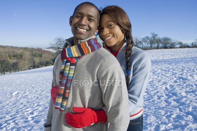 Marido y mujer abrazando en campo cubierto de nieve - foto de stock