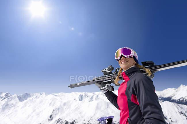 Femme souriante tenant des skis sur une montagne enneigée sous le soleil dans le ciel bleu — Photo de stock