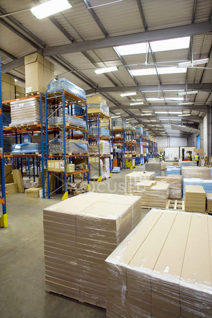 Cardboard boxes and pallets in warehouse — Stock Photo