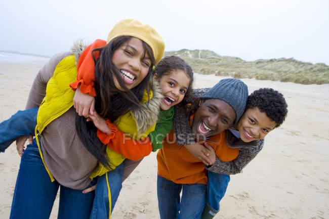 Parents piggybacking children on beach — Stock Photo