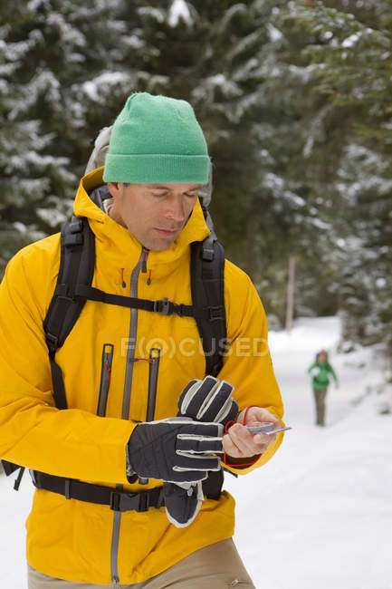 Man with backpack checking compass in snowy woods — Stock Photo