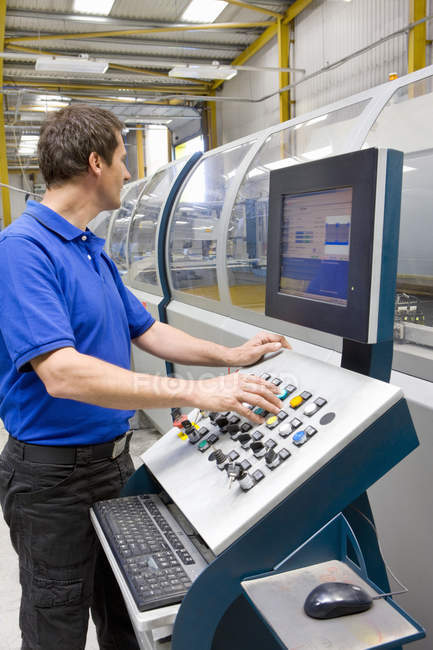 Lavoratore regolare pulsanti sul pannello di controllo di fabbrica — Foto stock
