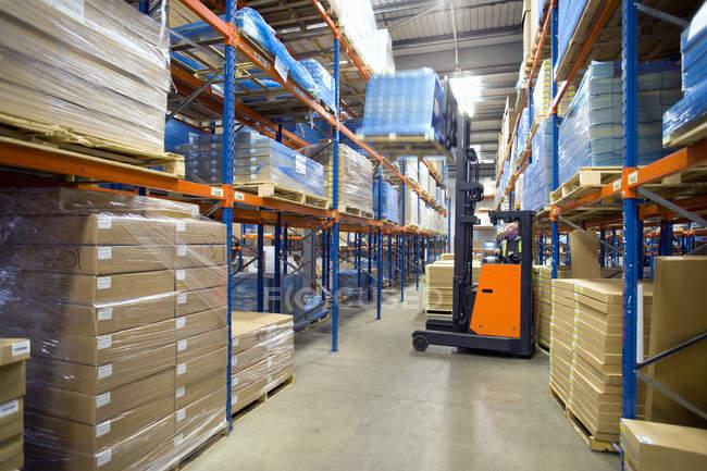 Склад працівник підйому коробки з полиці з навантажувач — стокове фото