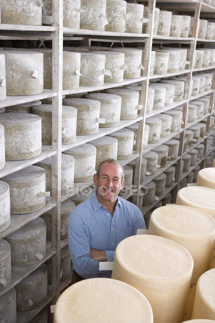 Portrait of smiling cheese maker standing among stacks of farmhouse cheddar cheese wheels in cellar warehouse — Stock Photo