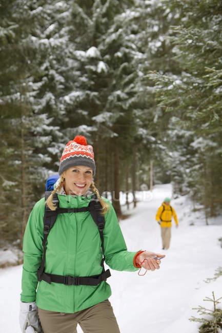 Ritratto di donna sorridente con lo zaino che tiene la bussola in boschi innevati — Foto stock