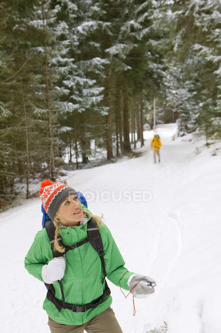 Woman with backpack holding compass in snowy woods — Stock Photo