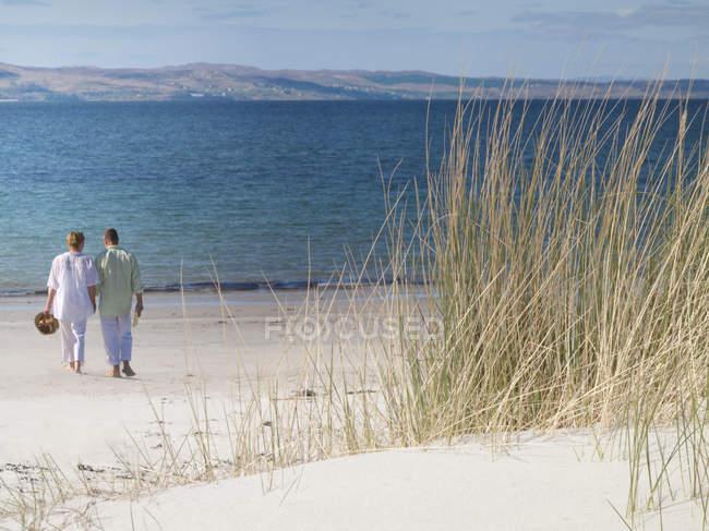 Vista traseira do casal caminhando na praia, perto do oceano tranquilo — Fotografia de Stock