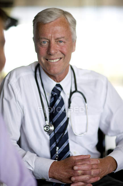 Doctor smiling and looking at camera — Stock Photo