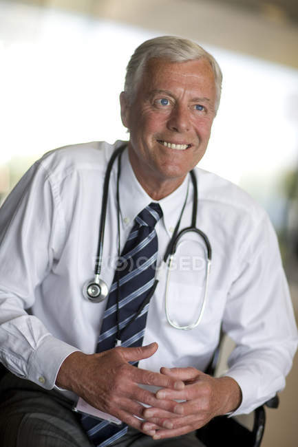 Senior doctor smiling and looking away — Stock Photo