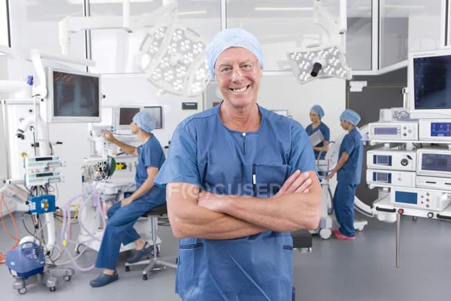 Vista frontal del cirujano hombre parado frente a sus colegas de trabajo en sala de operaciones del hospital - foto de stock