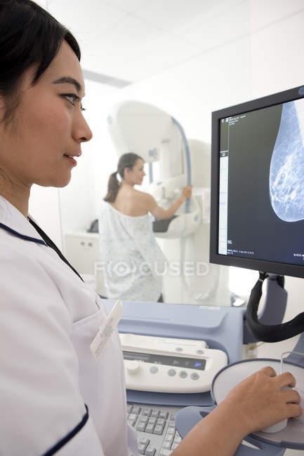 Radiologista olhando para exibição com mamografia — Fotografia de Stock