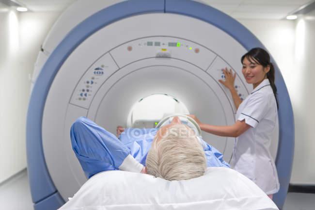 Радиолог, глядя на пациента лежа в МРТ — стоковое фото