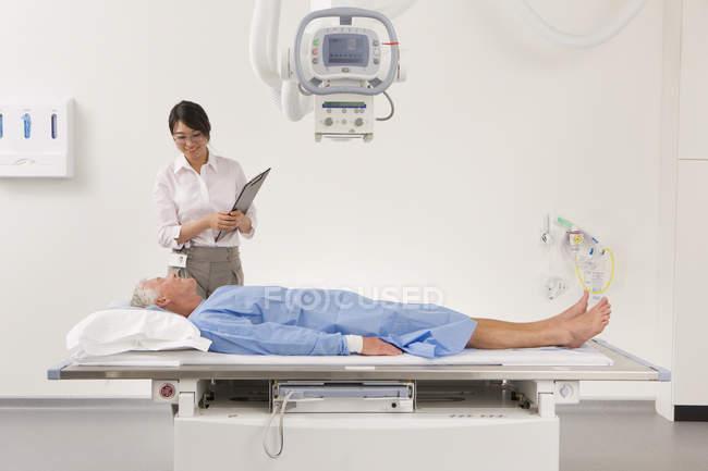 Врач-рентгенолог говорить пациента на рентгеновский аппарат — стоковое фото