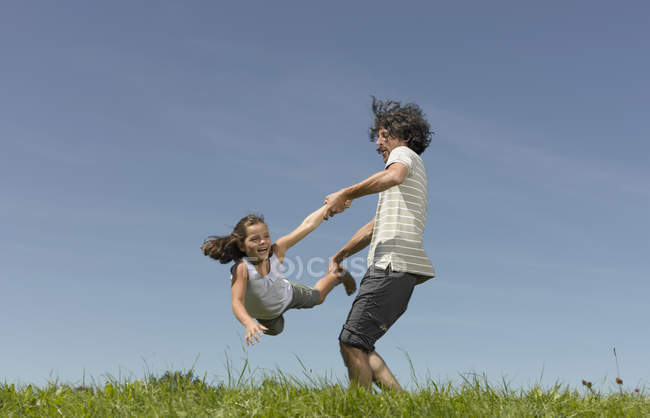 A father swinging his daughter through the air — Stock Photo