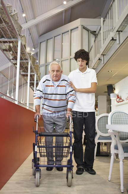 Ein älterer Mann, der einen Spaziergänger schubst, der von seinem Enkel unterstützt wird — Stockfoto