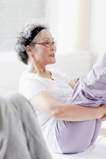 Senior woman holding legs in exercise class with defocussed background — Stock Photo
