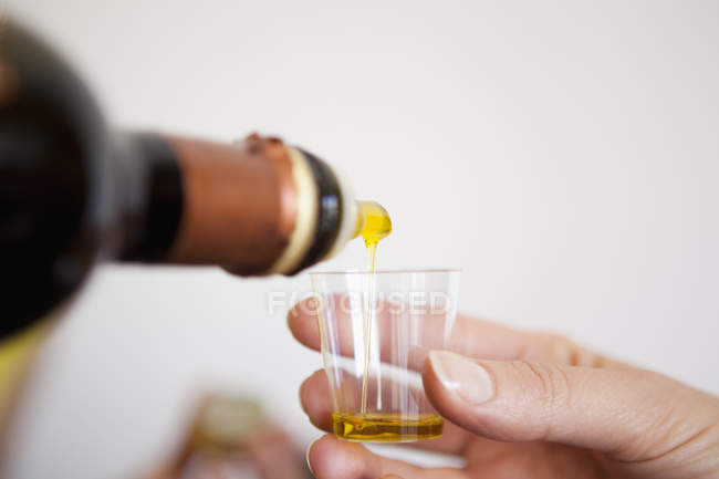 Pouring olive oil into a tasting cup — Stock Photo