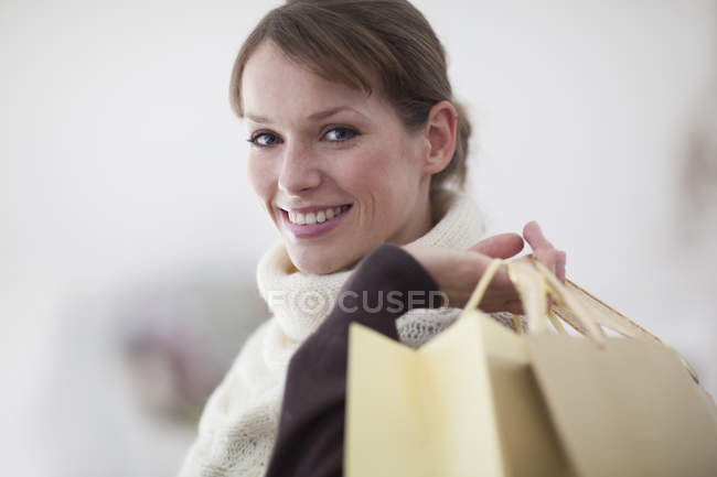 Woman holding shopping bags over shoulder — Stock Photo