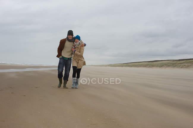 Couple marchant le long de la plage froide journée venteuse — Photo de stock
