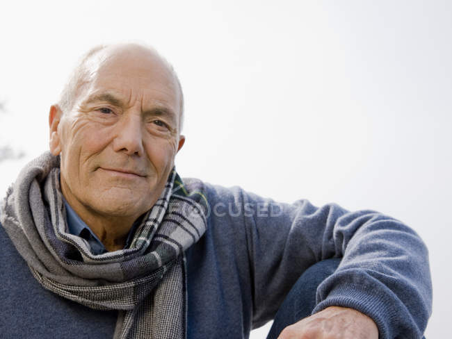 Portrait of a senior man wearing a blue sweater and scarf — Stock Photo