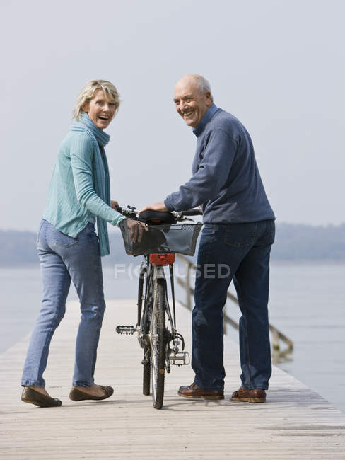 Senior couple pushing bicycle along wooden jetty — Stock Photo