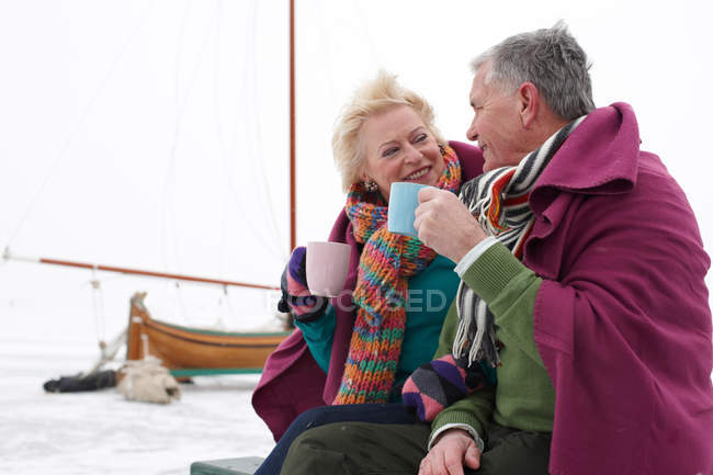 Senior couple drinking hot drinks on winter day — Stock Photo