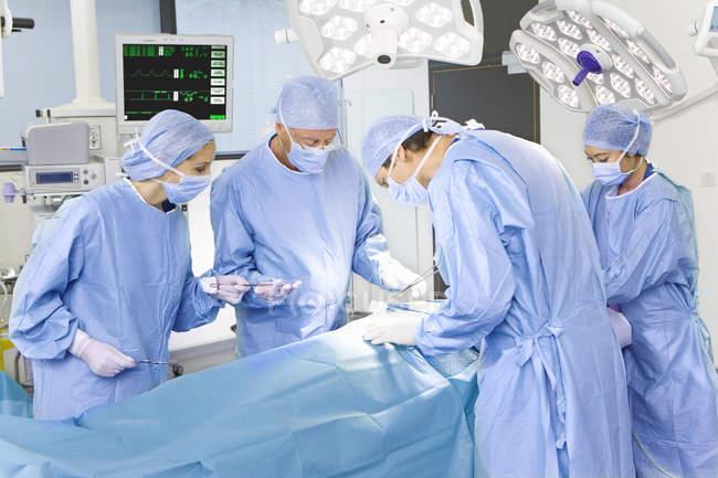 Cirujanos y enfermeras mirando hacia abajo - foto de stock