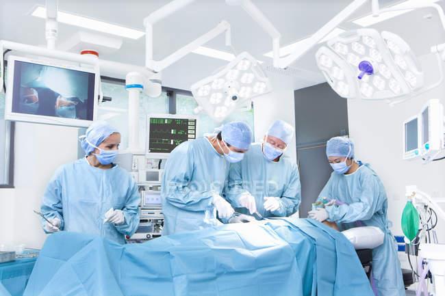 Chirurghi e infermieri paziente di funzionamento — Foto stock
