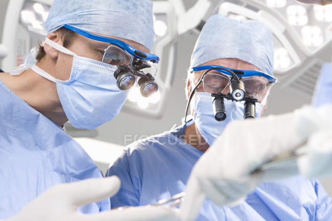 Surgeons in mask operating patient — Stock Photo