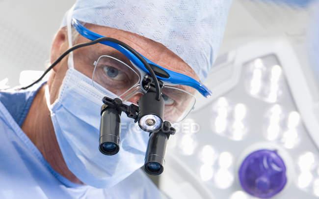 Cirurgião em máscaras e lupas, olhando para a câmera — Fotografia de Stock