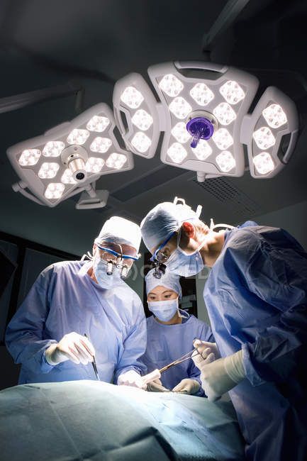 Surgeons in uniform performing operation — Stock Photo