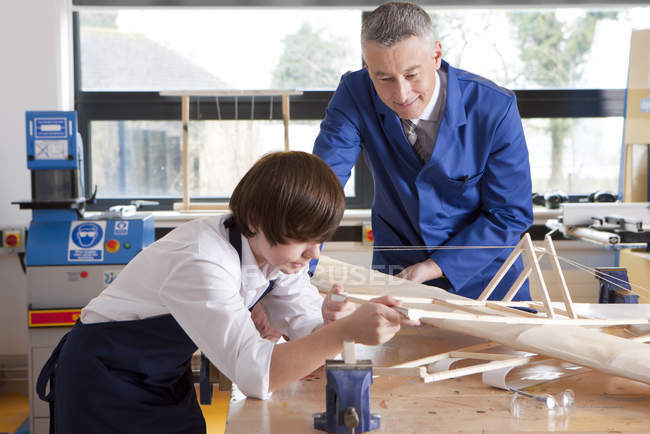 Teacher and student working on airplane model at table in woodworking class — Stock Photo