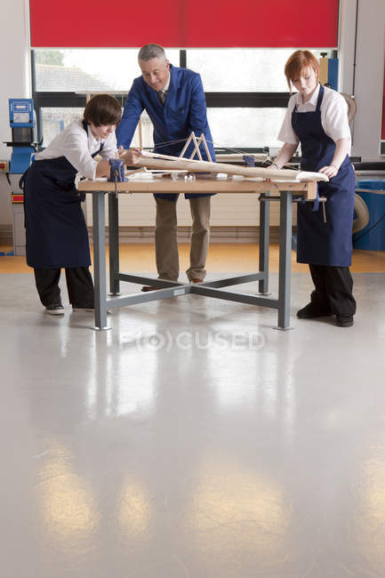 Teacher and students working on airplane model at table in woodworking class — Stock Photo