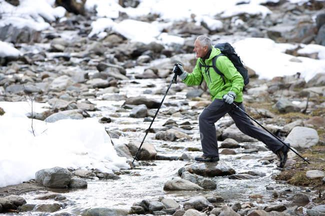 Ältere Mann mit Rucksack und Skistöcke Wildbach im verschneiten Wald — Stockfoto