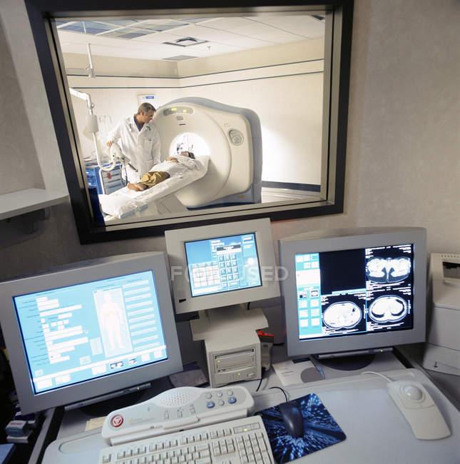 Дані та МРТ сканування на комп'ютерах з лікарем, дивлячись на пацієнта в магнітно-резонансної томографії у фоновому режимі — стокове фото