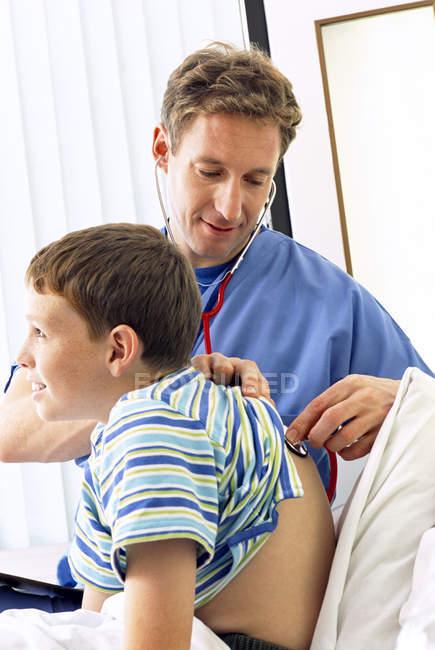 Доктор проверки мальчик дыхания с стетоскоп в больнице — стоковое фото