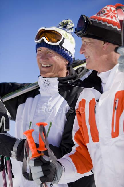 Lächelnd Skifahrer stehen zusammen auf Berggipfel — Stockfoto