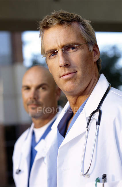 Close up portrait of serious doctors in lab coats — Stock Photo
