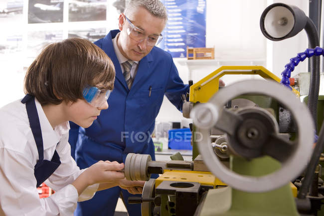 Portrait of teacher watching student using lathe in metalwork class — Stock Photo