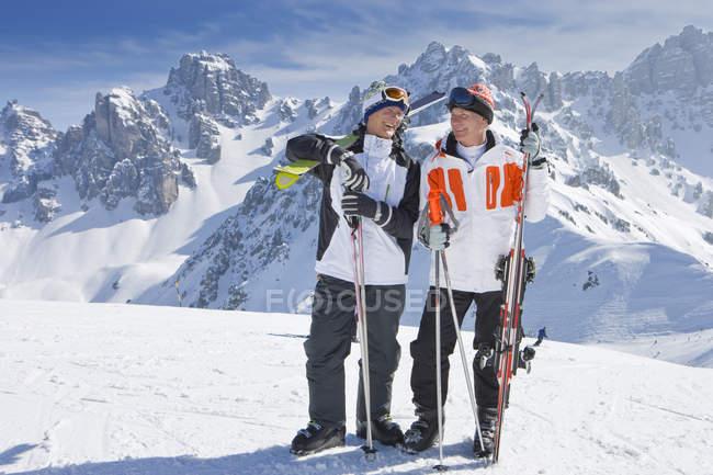 Улыбаясь старшие мужчины с лыжами на снежные горы — стоковое фото