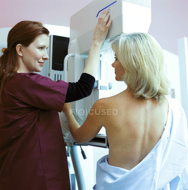 Nurse helping woman with mammogram in clinic — Stock Photo