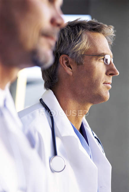 Close up of pensive doctors in lab coats — Stock Photo
