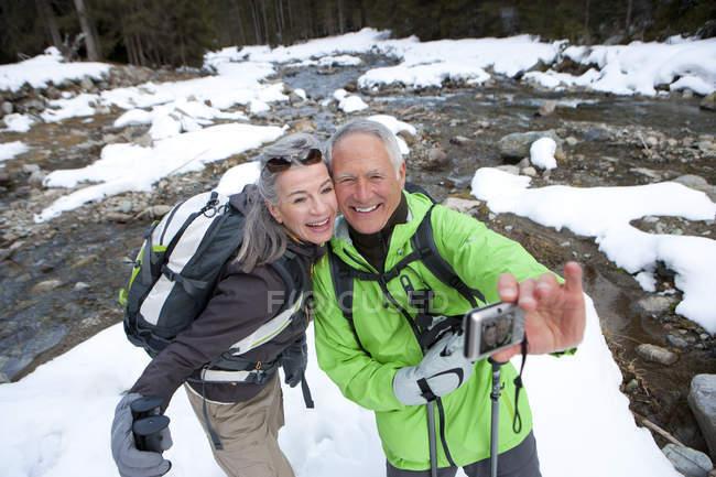Paar mit Rucksäcken und Skistöcke unter Self-Portrait in der Nähe von verschneiten stream — Stockfoto