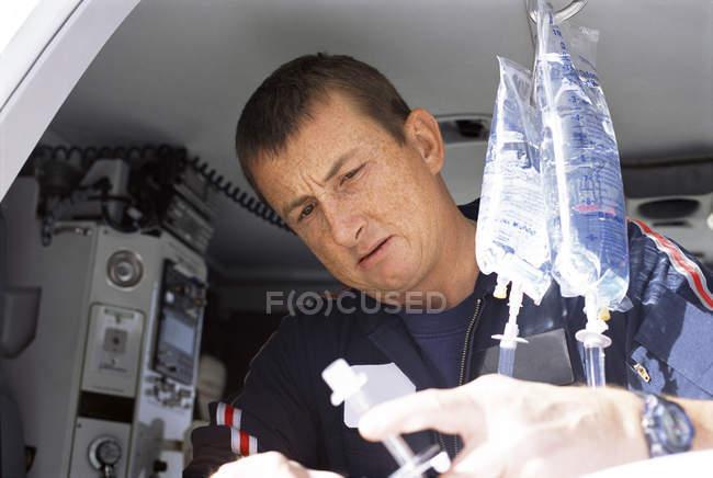 Gros plan des paramédicaux travaillant avec saline intraveineuse dans l'hélicoptère de transport aérien d'urgence — Photo de stock
