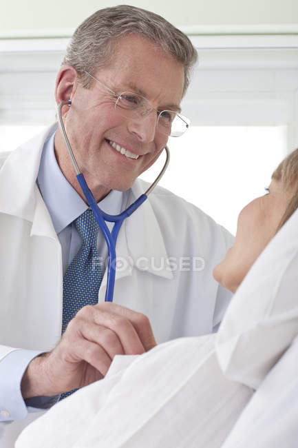 Doctor listening to patient heartbeat in hospital room — Stock Photo