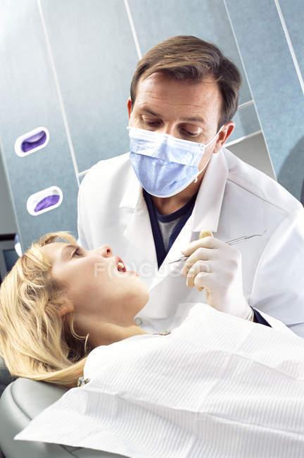 Zahnarzt suchen in Mädchen in den Mund — Stockfoto