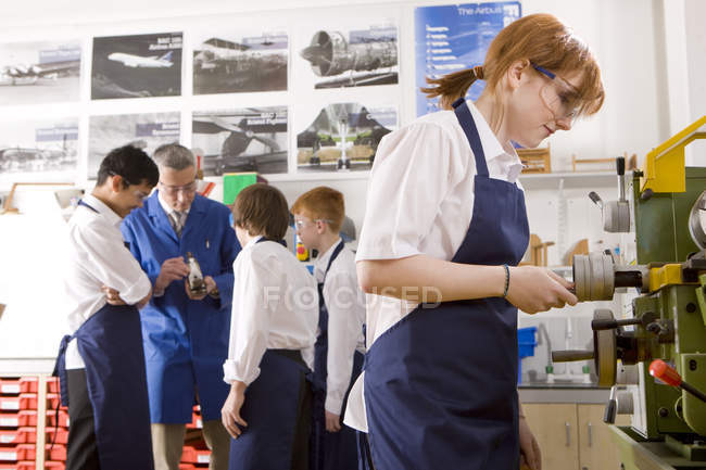 Side view of female student using lathe in metalwork class over teacher talking to group of students on background — Stock Photo