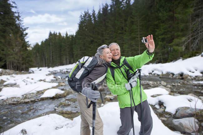 Paar mit Rucksäcken und Skistöcke unter Selbstporträt im verschneiten Wald — Stockfoto