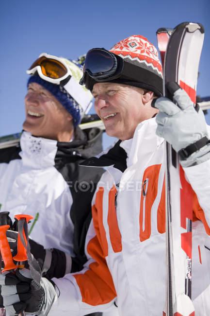 Lächelnde Skifahrer zusammenstehen — Stockfoto