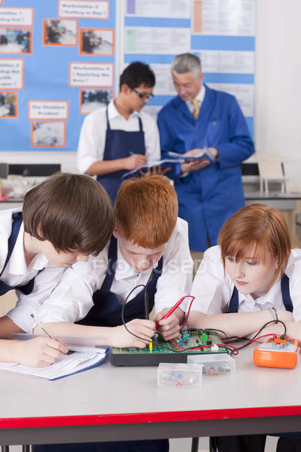 Portrait of three students working on electronic measuring device over teacher talking with boy in vocational class — Stock Photo